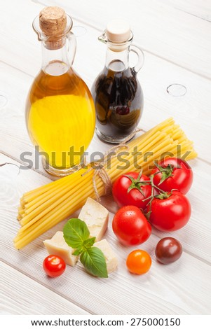 Italian food cooking ingredients. Pasta, tomatoes, basil on wooden table  - stock photo