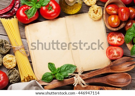Italian food cooking. Tomatoes, basil, spaghetti pasta, olive oil and cookbook for your recipe on wooden kitchen table. Top view with copy space - stock photo