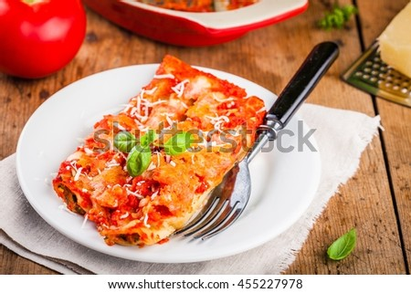 Italian food: homemade cannelloni with spinach and tomato sauce