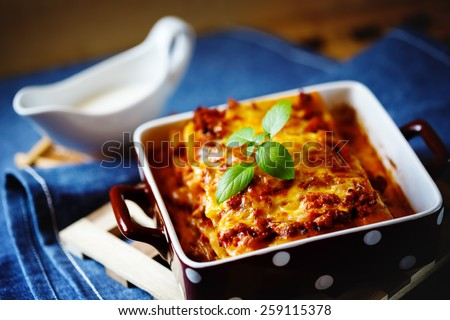 Italian Food. Hot tasty Lasagna plate served with fresh basil leaf and white sauce. - stock photo