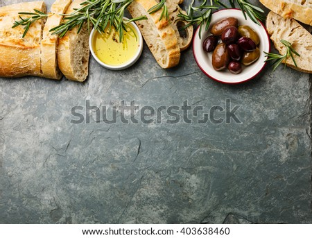 Italian food ingredients background with Sliced bread Ciabatta, olive oil, olives and rosemary on gray stone slate - stock photo