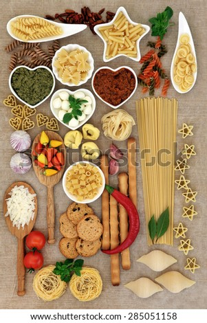 Italian food ingredients including pasta, herb and spice selection, pesto, parmesan and mozzarella cheese over brown paper background. - stock photo