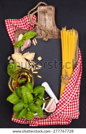 Italian Food. Italian pasta and pesto ingredients on black slate board. - stock photo