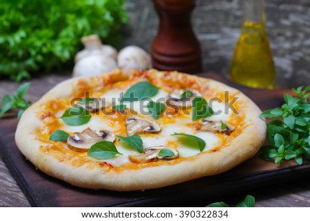 Italian food. Mediterranean cuisine. Delicious pizza with mushrooms and basil - thin pastry crust on wooden background.