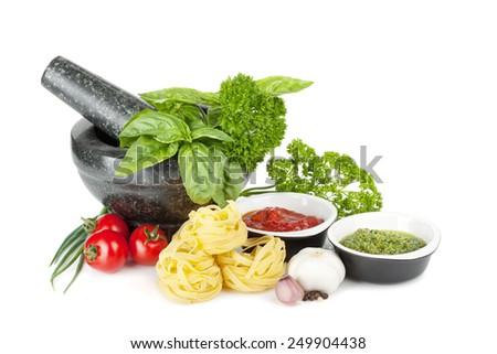 Italian food: pasta, tomatoes, fresh herbs in mortar, pesto. Isolated on white background - stock photo
