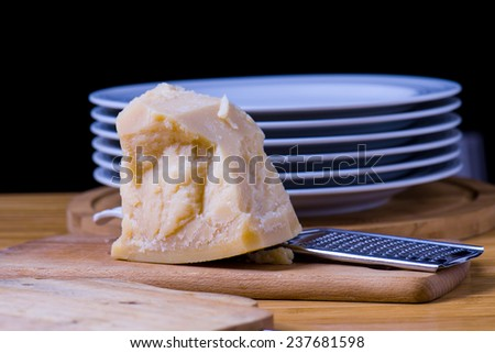italian food: slice of cheese called parmesan with grater and dishes on background - stock photo