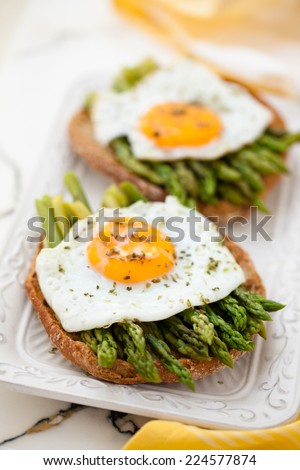 Italian food: snack with asparagus and fried eggs. - stock photo