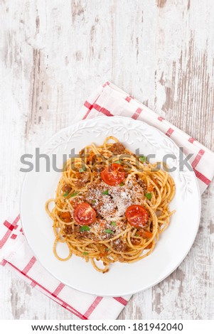 Italian food - spaghetti bolognese on white wooden table, top view, vertical - stock photo