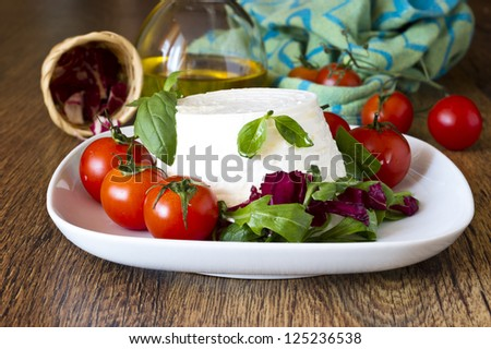 italian fresh ricotta with tomatoes and salad on wooden table