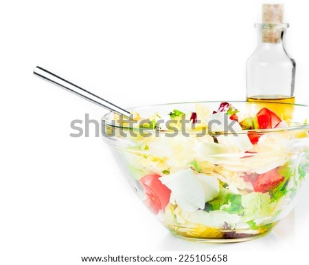 Italian fresh salad with fork isolated in front of olive oil bottle on white background diet concept - stock photo