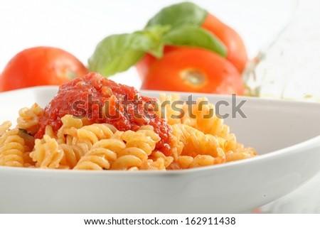 Italian fusilli pasta with tomato sauce on a white background - stock photo