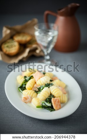 Italian gnocchi pasts served with salmon and basil on an oval platter with a glass of white wine and toasted herb buns - stock photo