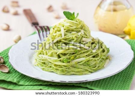 Italian green pasta spaghetti with pesto green peas, mint, pistachios, parmesan cheese, delicious healthy vegetarian appetizer - stock photo