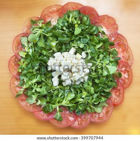 Italian green salad with tomato, corn salad and mozzarella - stock photo