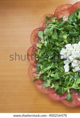 Italian green salad with tomato, oil, oregano, lettuce and cheese - stock photo
