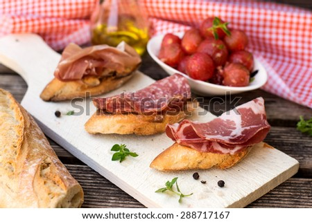 Italian ham dry cured prosciutto on bread toast with coppa and salami. Selective focus