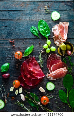 Italian ham, prosciutto and salami. Ingredients for bruschetta, crostini or sandwich bar. Rustic top view of ingredients. Ham with vegetables and spices - stock photo