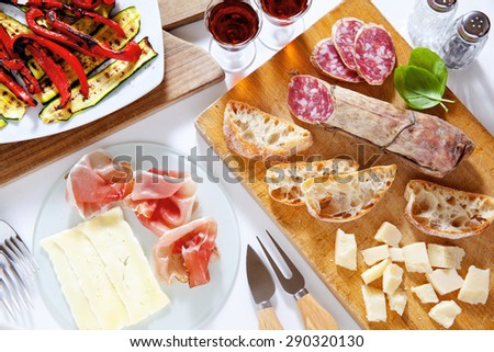 Italian healthy snacks. prosciutto, salami, vegetables grilled peppers and zucchini, parmesan cheese, fresh sliced bread ciabatta, ripe basil, and Marsala wine in glasses. Summer breakfast or lunch - stock photo