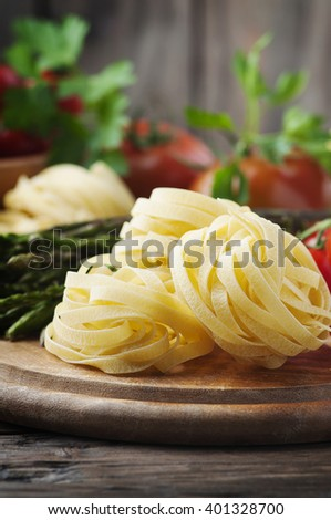 Italian homemade pasta with raw asparagus, selective focus - stock photo