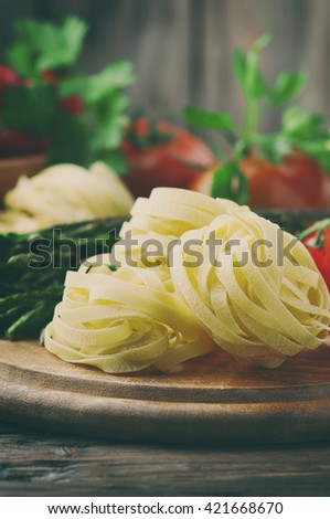 Italian homemade pasta with raw asparagus, selective focus and toned image - stock photo