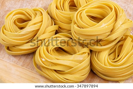 Italian homemade rolled raw fettuccine pasta with flour on wooden cutting board. - stock photo