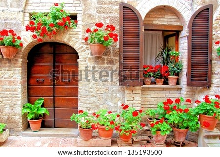 Italian house front with colorful potted flowers            - stock photo