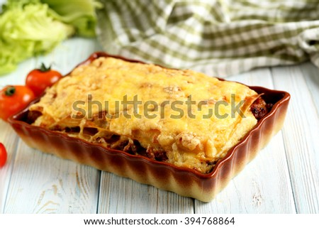 Italian lasagna in bowl on a blue wooden table