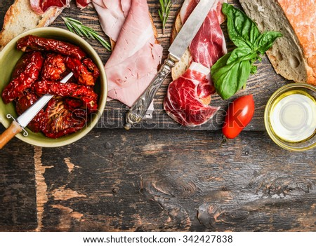 Italian meat plate with bread and antipasti on rustic wooden background, top view. Italian food - stock photo