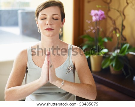 italian 6 months pregnant woman doing yoga exercise at home. Horizontal shape, head and shoulders, front view - stock photo