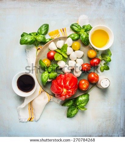 Italian mozzarella tomatoes salad, ingredients with oil and  balsamic vinegar on rustic wooden background, top view - stock photo