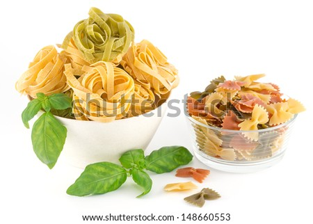 Italian pasta and basil leaves isolated on white background