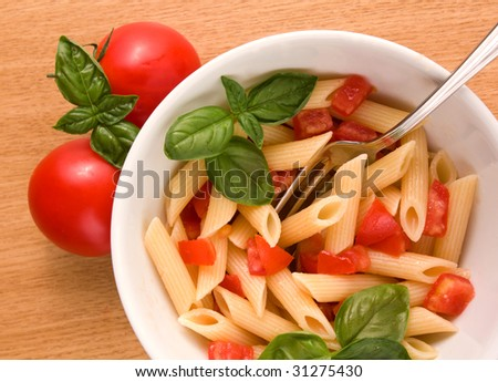 Italian pasta and fresh tomatoes on the table - stock photo