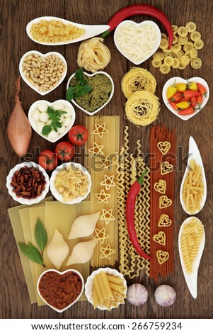 Italian pasta and mediterranean food ingredients forming an abstract background over oak. - stock photo