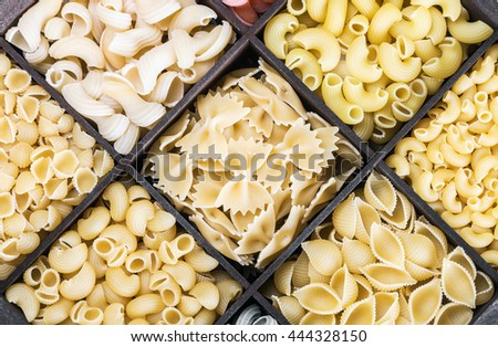 Italian pasta assortment background. Pasta in a wooden box. Italian pasta of different colors - stock photo