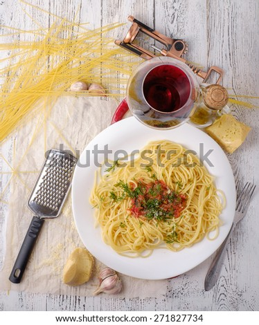 Italian pasta cooked in a rustic style with a sauce of fresh tomatoes and garlic on a wooden table with a glass of red wine.  - stock photo