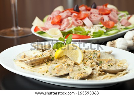 Italian pasta dish with fresh clams over pasta with herbs and cheese.  Shallow depth of field.
