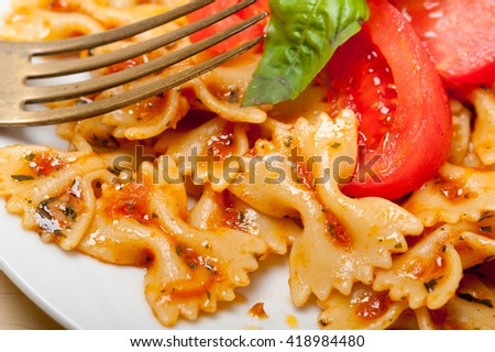 Italian pasta farfalle butterfly bow-tie with tomato basil sauce over white rustic wood table - stock photo