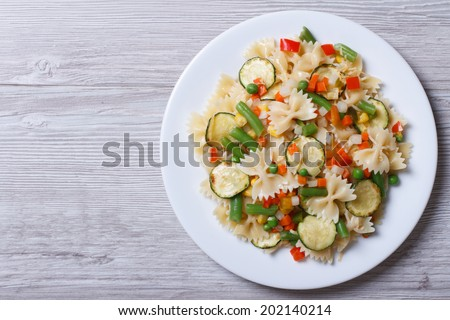 Italian pasta farfalle with slices of vegetables on a wooden background. horizontal top view   - stock photo