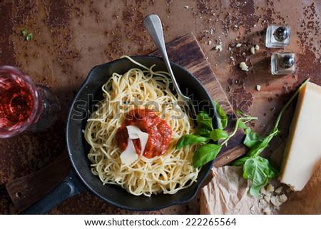 Italian pasta food (spaghetti, Parmesan, wine, rose and fresh herbs) - stock photo