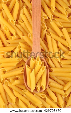 Italian pasta penne in a wooden spoon