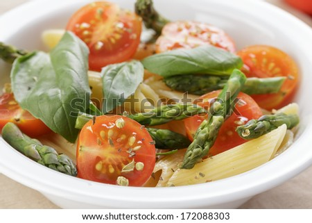 italian pasta penne with tomatoes and asparagus, on table