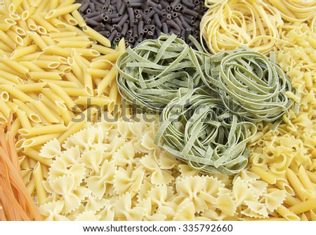 Italian Pasta raw food collection. different kinds of colorful pasta composition. Raw green close-up tagliatelle