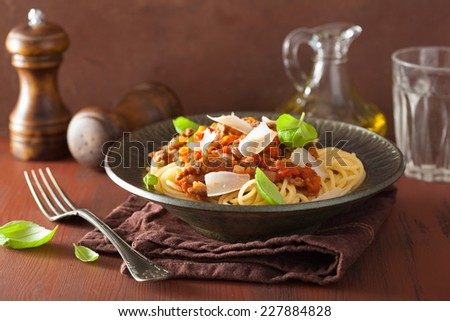italian pasta spaghetti bolognese with basil on rustic table - stock photo