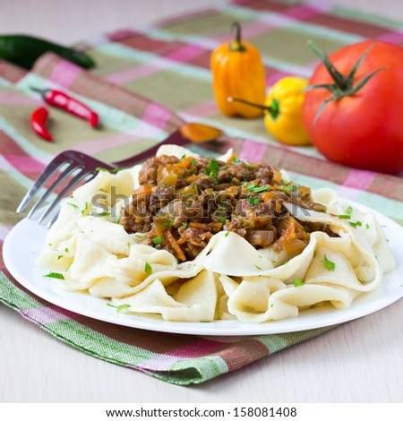 Italian pasta tagliatelle with meat sauce and vegetables, homemade Bolognese - stock photo