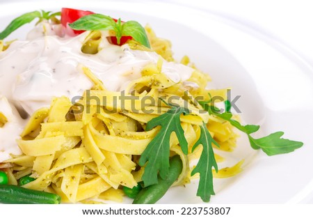 Italian pasta with basil. Isolated on a white background.