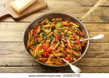 Italian pasta  with  chili sauce  on rustic wooden table