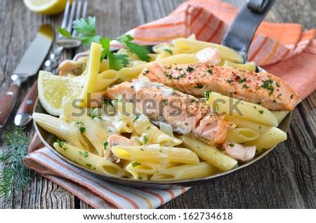 Italian pasta with fried salmon fillet stripes and salmon cream sauce - stock photo
