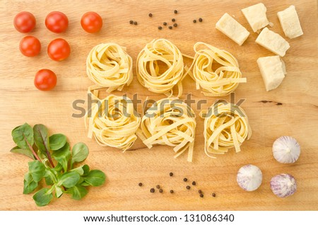 Italian pasta with ingredients on a wooden cutting board - stock photo