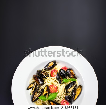 Italian pasta with Mussels marinara, cherry tomatoes and herbs for a tasty seafood meal over black table with copy space, close up   - stock photo
