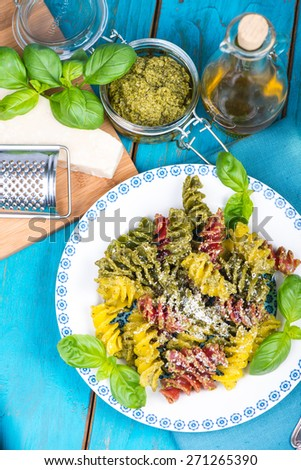 Italian pasta with pesto and fresh basil served on plate - stock photo